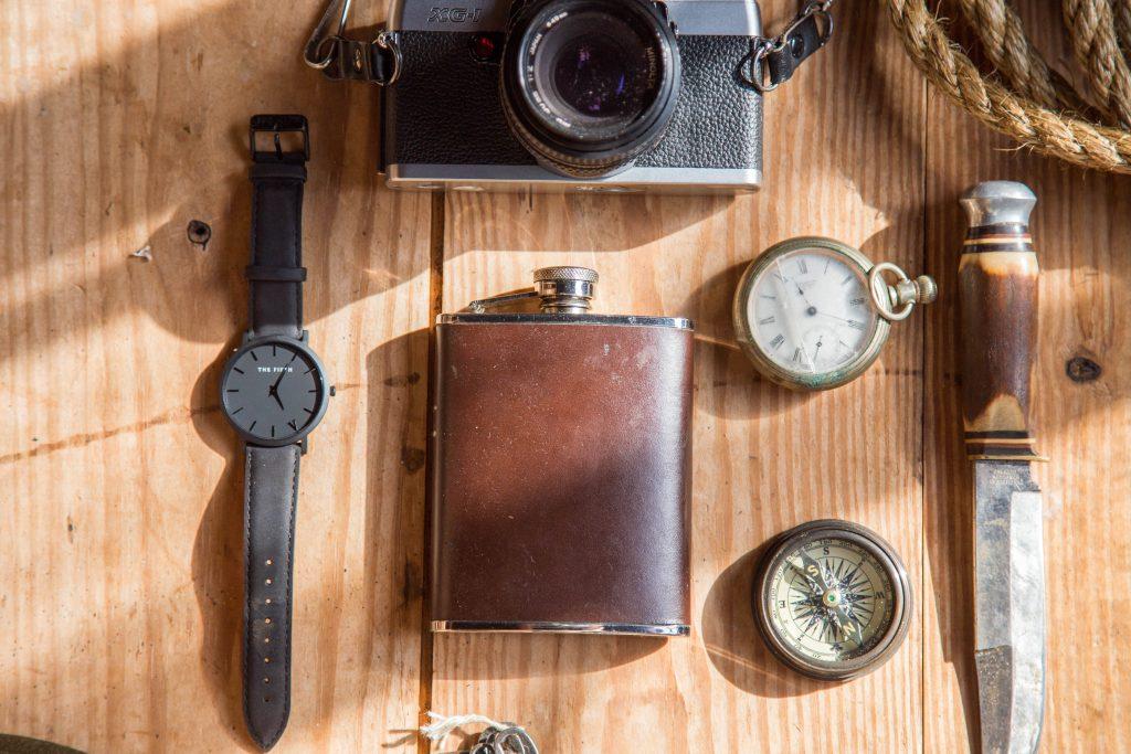 Na imagem está uma faca, uma bussola, dois relógios, uma câmera e um cantil em uma mesa de madeira.