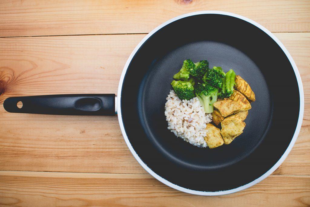 Na foto uma frigideira com frango, brócolis e arroz.