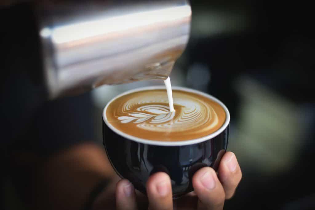 Leite sendo despejado na caneca com leiteira para fazer latte art.