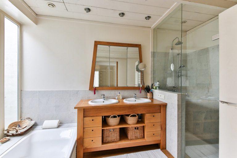 Na foto um banheiro com box, armário em madeira, espelho e banheira.