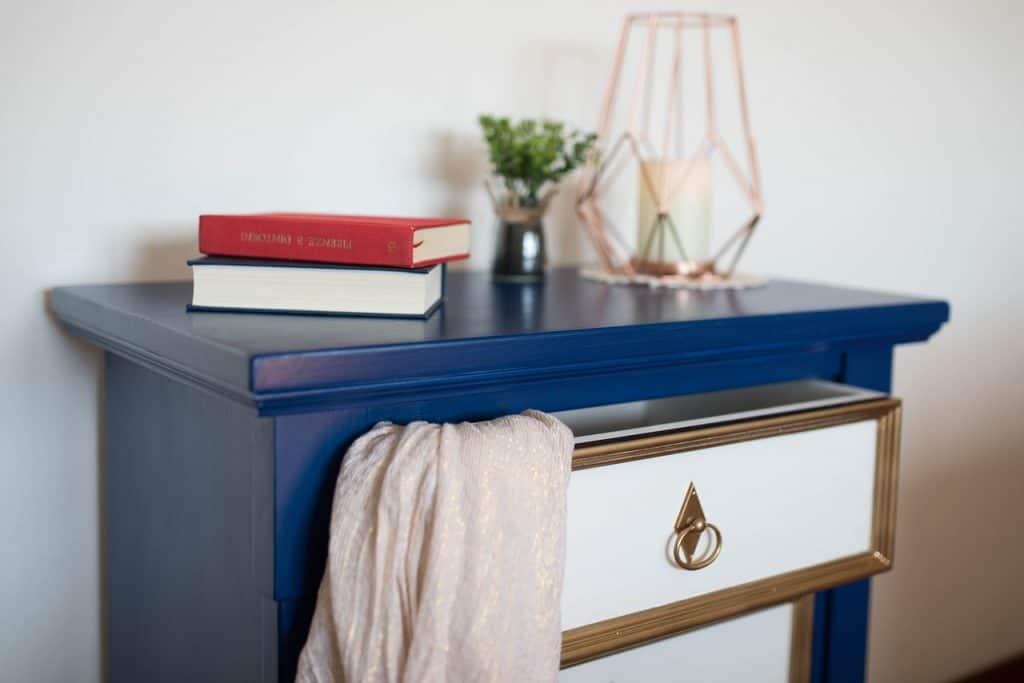 Imagem de um gaveteiro azul. No tampo há dois livros, uma planta e uma vela decorativa.