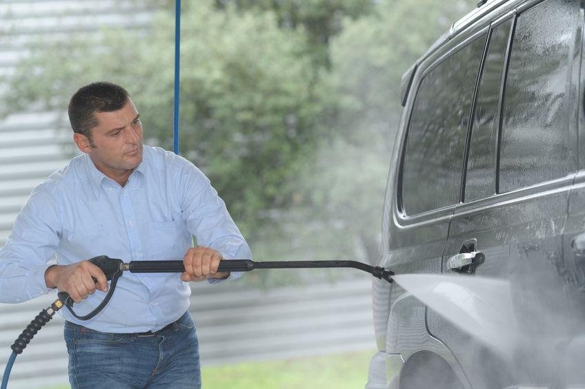 Imagem mostra um homem usando uma mangueira de alta pressão para lavar um carro.