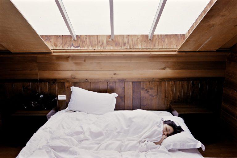 Mulher deitada em cama de casal em quarto com paredes de madeira e clarabóia no teto