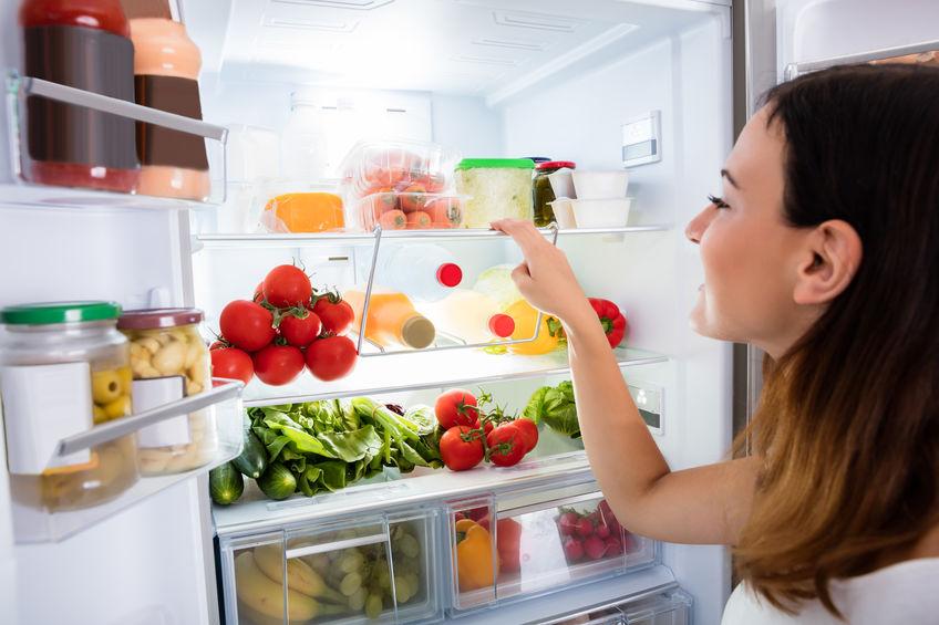 Mulher com a porta da geladeira aberta escolhendo alimentos.