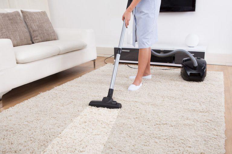 Imagem de pessoa limpando o carpete com um aspirador de pó