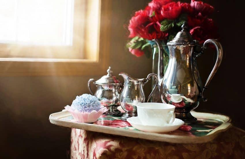Imagem mostra um conjunto de chá numa bandeja, com um bule metálico em destaque, no canto de uma sala, ao lado de uma janela e de um vaso de flores.
