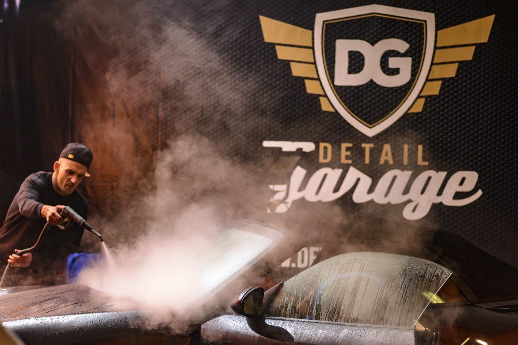 Imagem mostra um homem lavando um carro com uma mangueira de alta pressão.