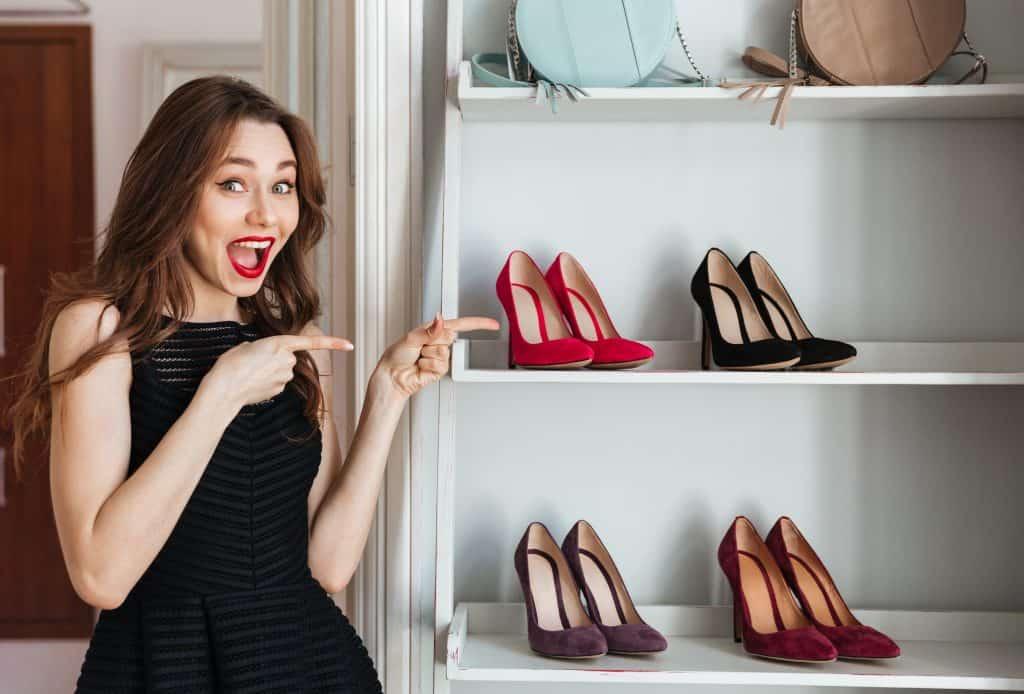 Mulher ao lado de sapateira com sapatos de salto alto.