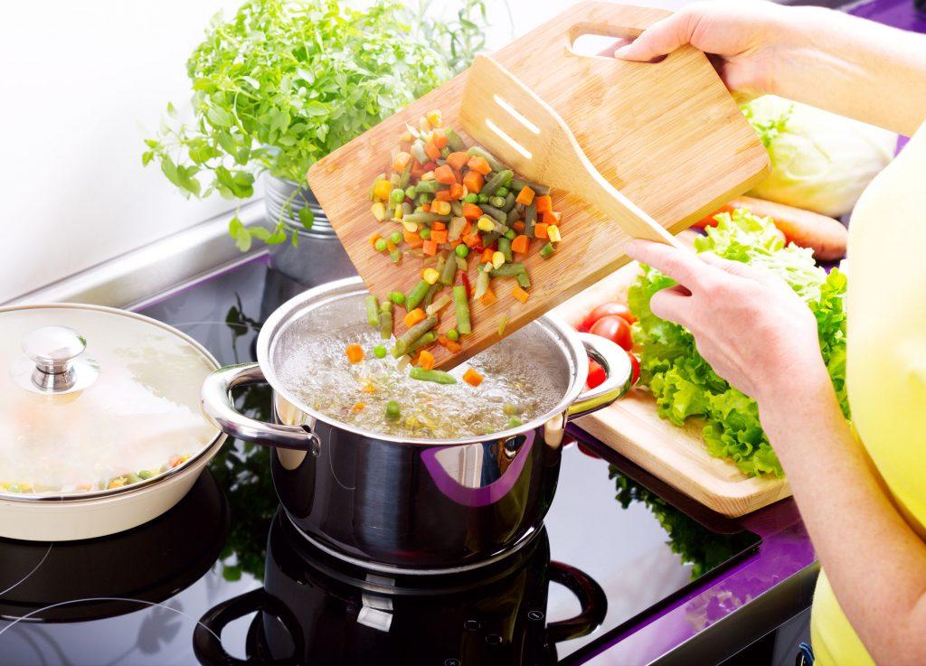 Na foto uma mulher cozinhando legumes com duas panelas no cooktop.