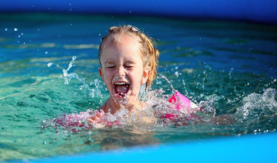 Menina de olhos fechados e sorrindo em uma piscina inflável.