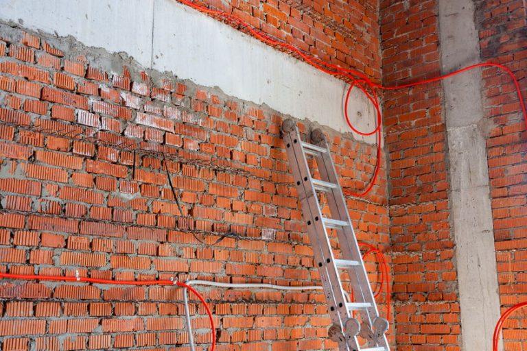 Imagem mostra uma escada multifuncional em uma área cheia de tijolos.