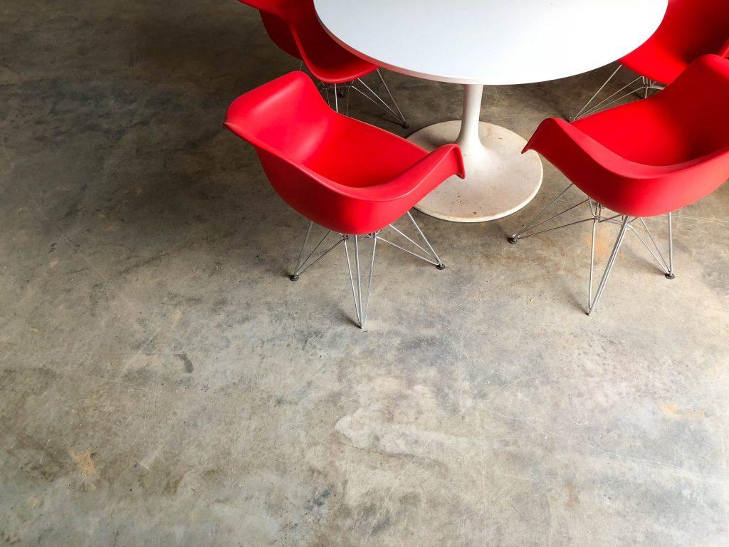 Mesa branca e redonda vista de cima com cadeiras vermelhas.