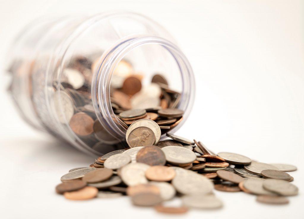 Um cofrinho em formato de jarra sem a tampa está derrubado e esparramando as moedas para fora dele.