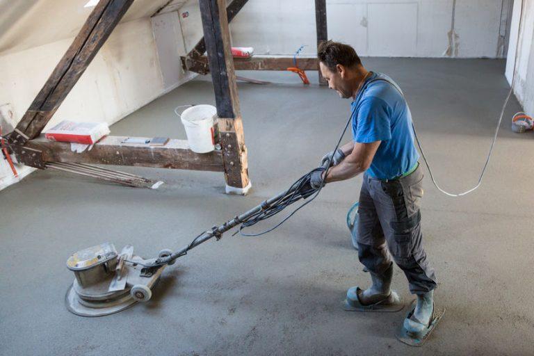 Imagem mostra um homem usando uma enceradeira industrial para polir cimento.