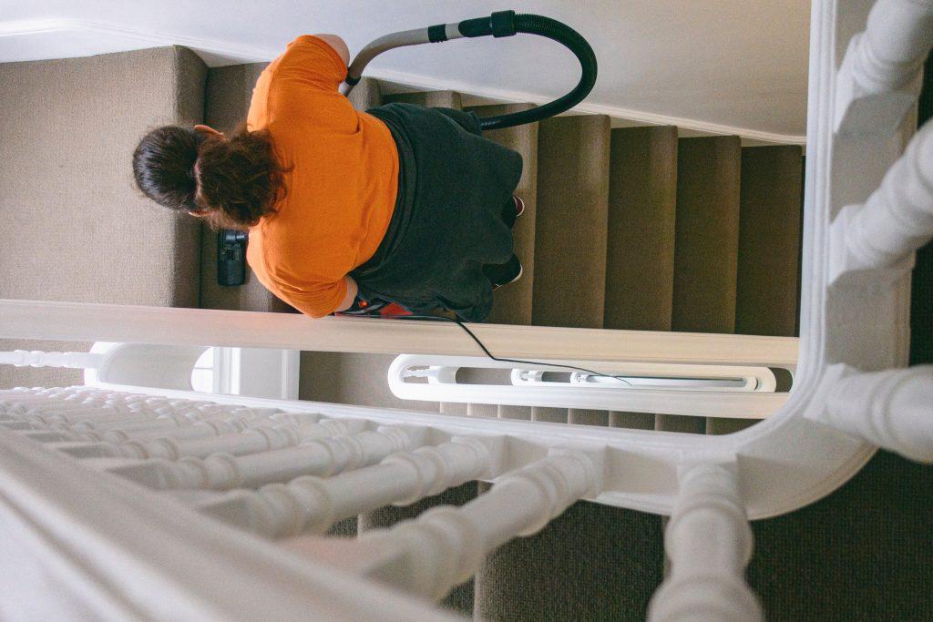 Imagem de mulher limpando escadas com um aspirador de pó