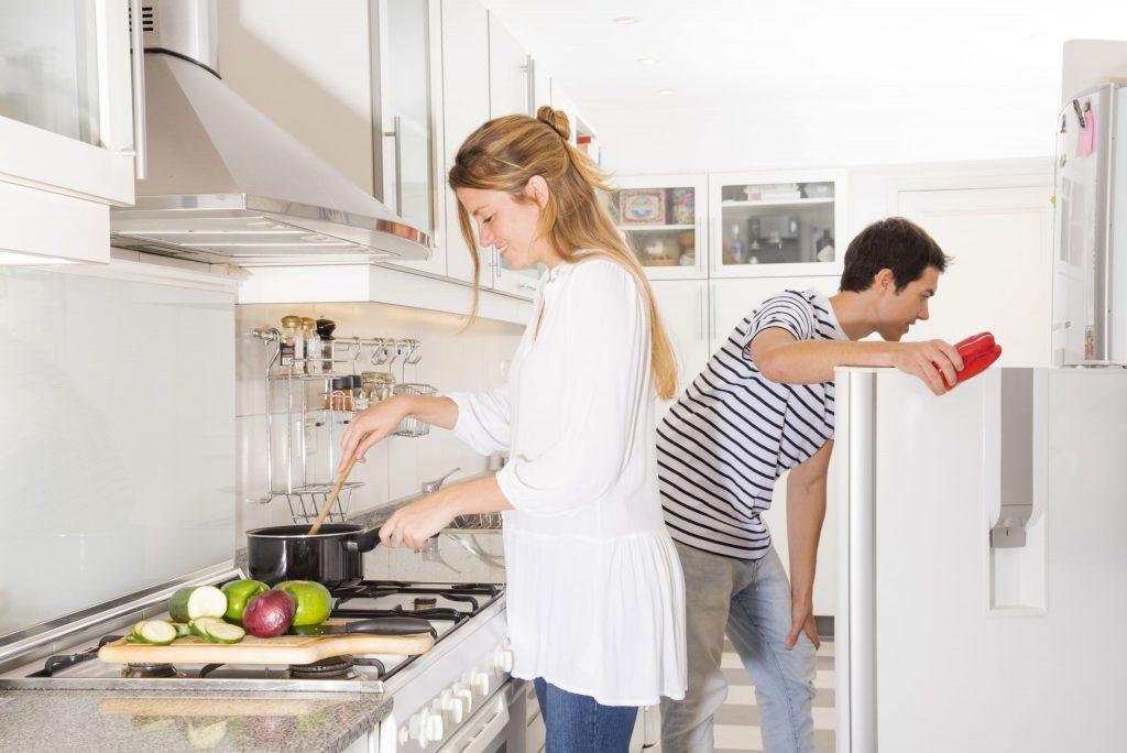 Mulher cozinha enquanto homem procura ingredientes na geladeira
