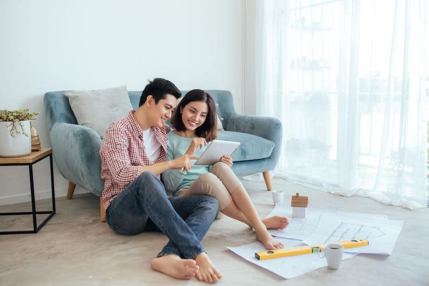 Casal sentado encostado no sofá no chão da sala mexendo em papéis.