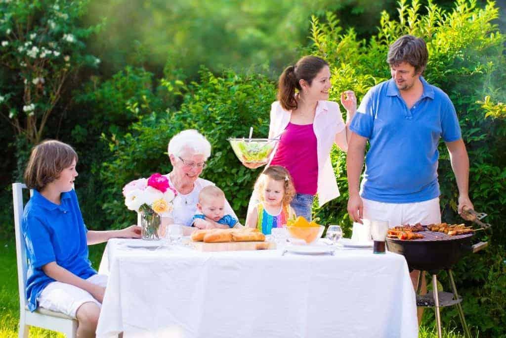 Imagem mostra família reunida no jardim para um churrasco ao ar livre.
