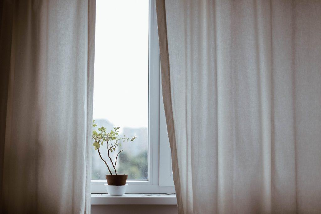 Foto de uma cortina semi aberta, com janela fechada e um pequeno vaso de planta na beirada na janela.