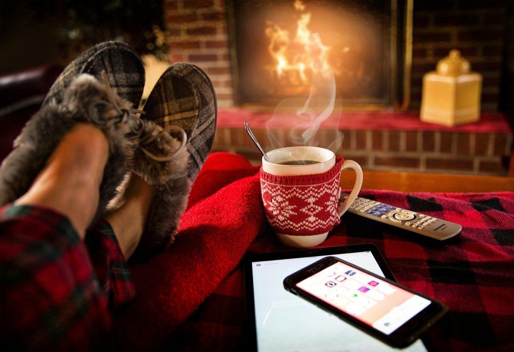 Na foto os pés de uma pessoa em frente a uma lareira com um xícara de café ao lado.