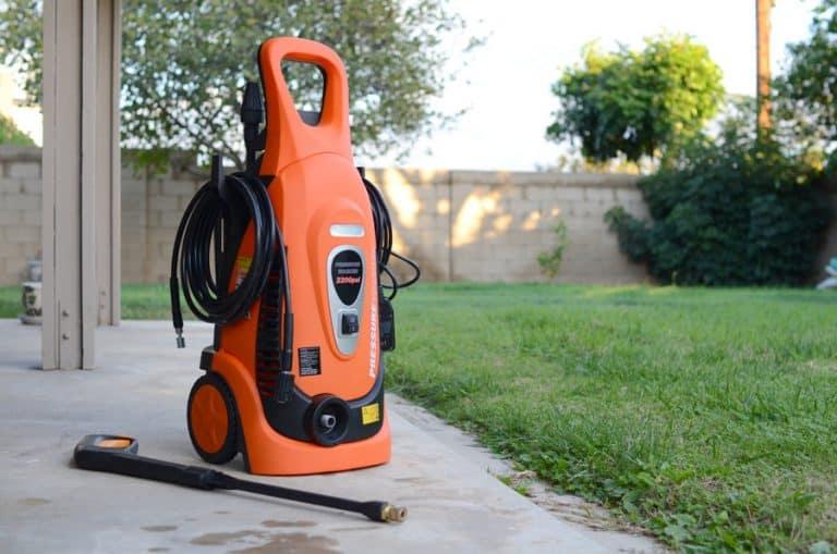 Na foto uma lavadora de alta pressão em um quintal.