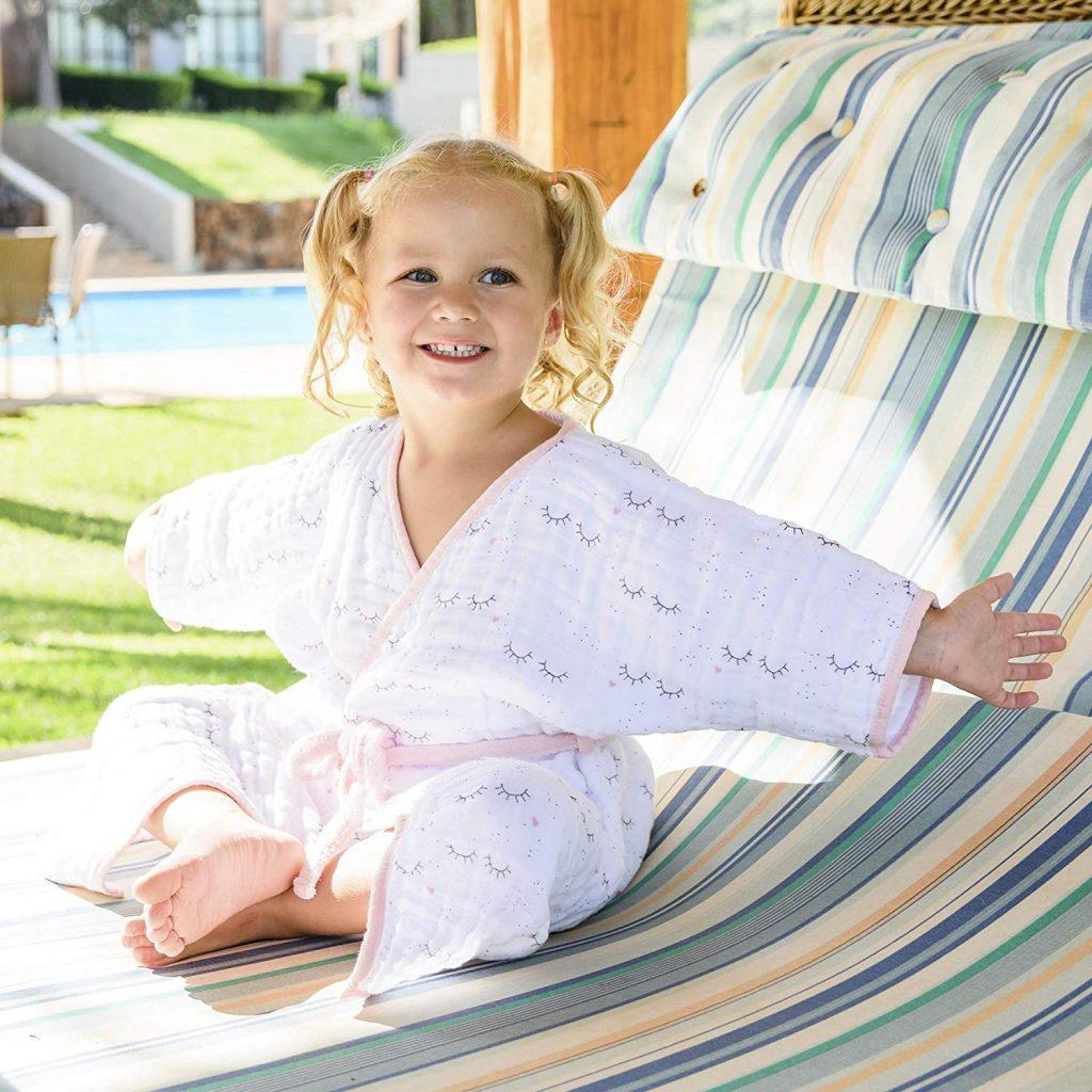 Menina envolvida com roupão infantil de fralda sentada em cadeira após saída da piscina.