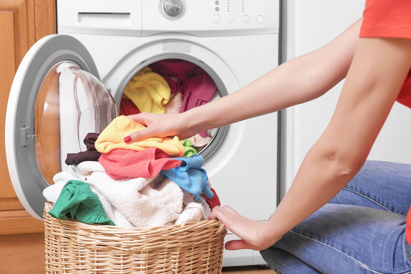 Pessoa mudando ciclo de lavagem em máquina de lavar. Link: