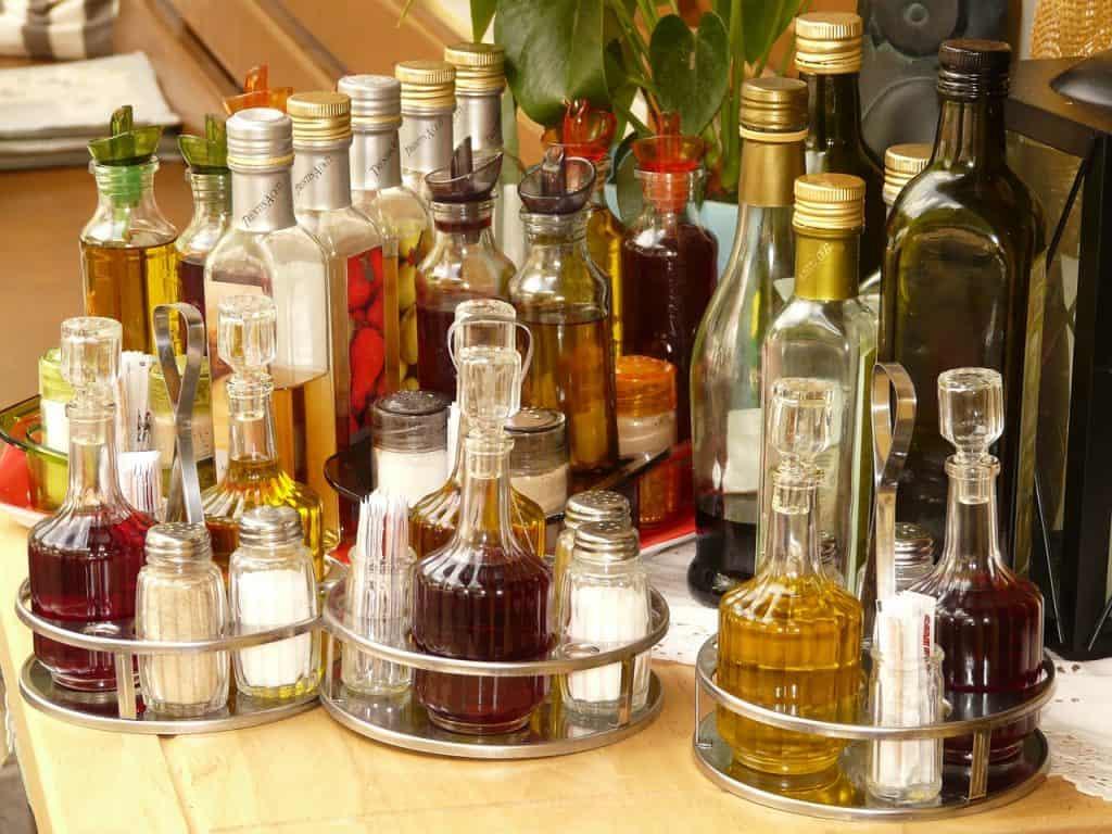 Na foto três galheteiros em cima de uma mesa com diversas garrafas de azeite ao fundo.