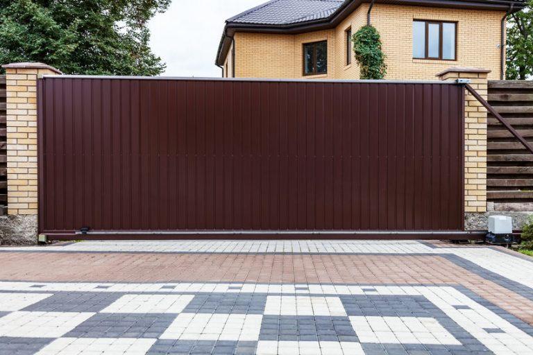 Imagem de uma grande casa de tijolinhos com portão eletrônico deslizante cobrindo boa parte dela.