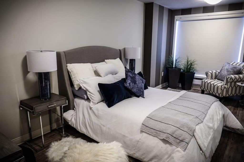 Mesinha de canto quadrada com um abajur em cima ao lado de uma cama.