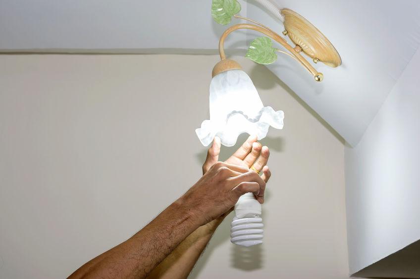 Mãos substituem lâmpada comum por fluorescente