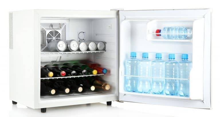 Frigobar aberto com garrafas e latas.