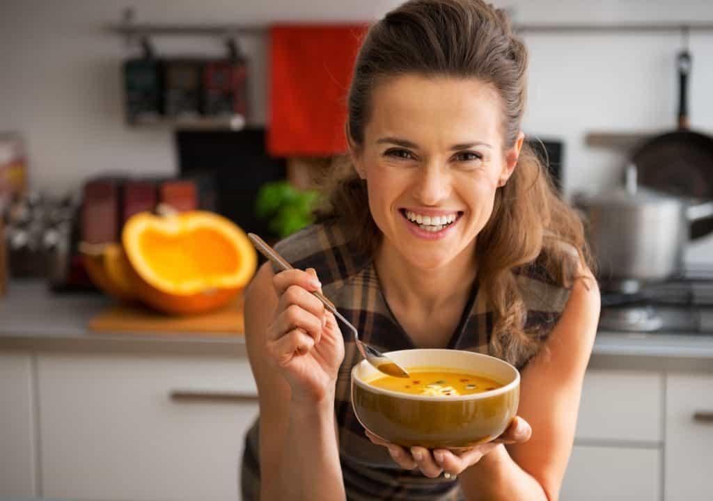Na foto uma mulher dentro de uma cozinha com um bowl de sopa em uma mão e uma colher na outra.