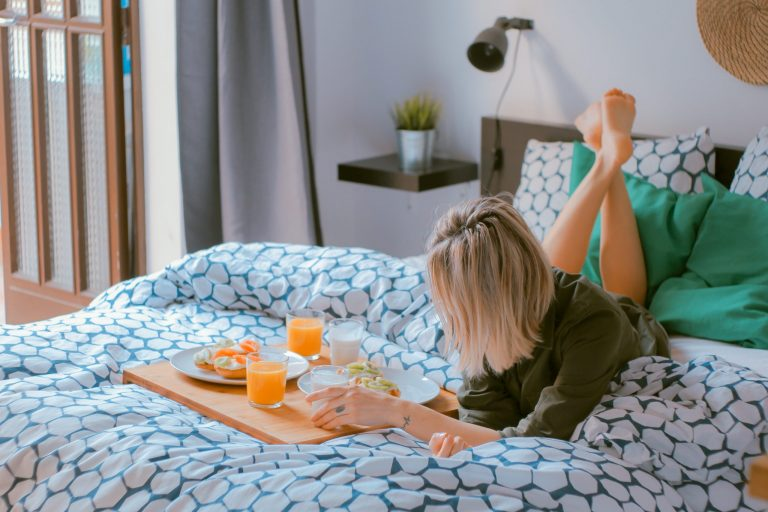Na foto uma mulher deitada em uma cama com uma bandeja de café da manhã em sua frente.