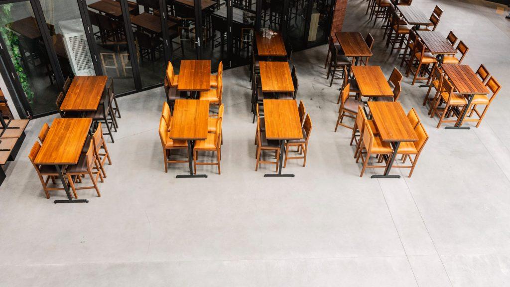 Vista de cima de uma restaurante vazio com mesas e cadeiras de madeira.