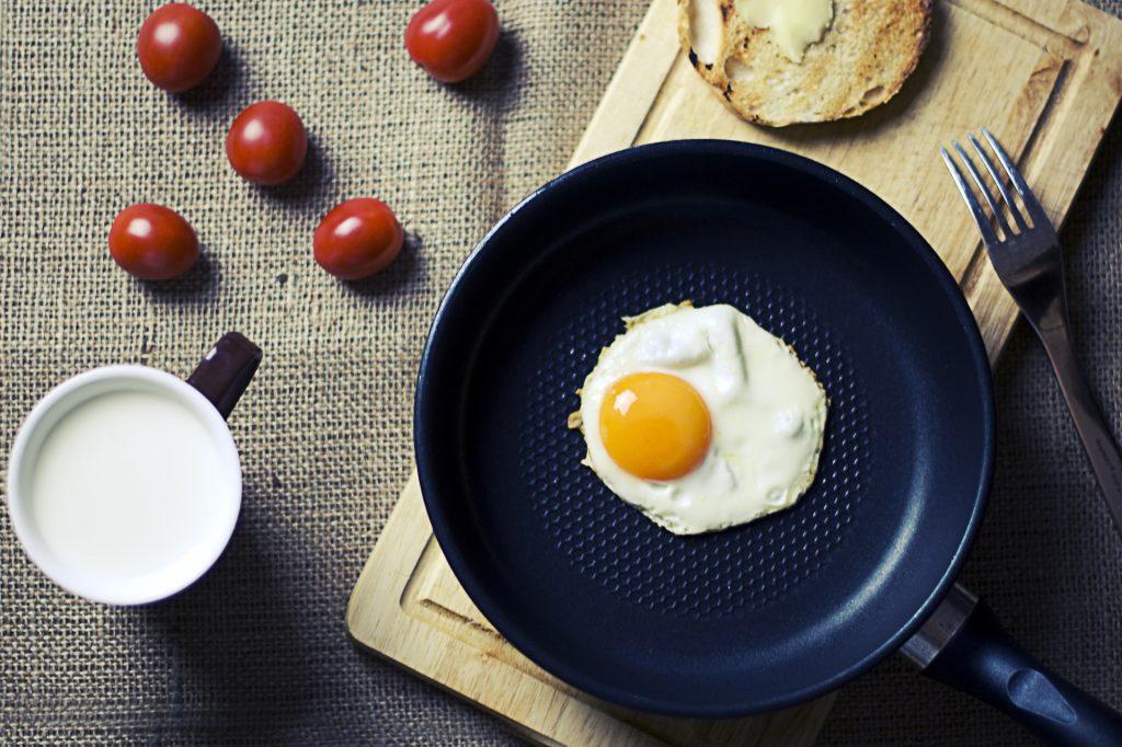 Na foto uma frigideira com um ovo dentro em cima de uma tábua, com tomates, pães e uma xícara ao lado.