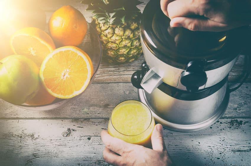 Na foto um espremedor de laranja com uma pessoa segurando um copo de suco ao lado e algumas frutas ao redor.