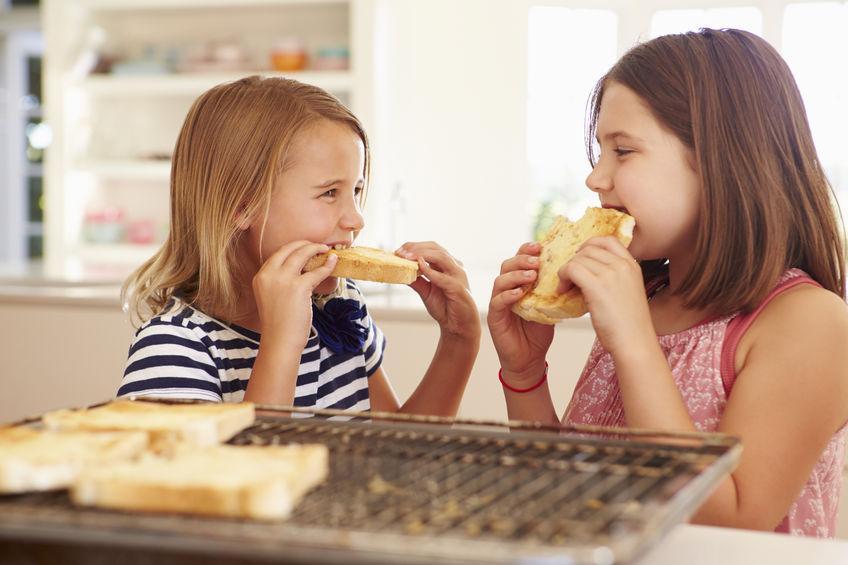 duas garotas comendo sanduíches tostados.