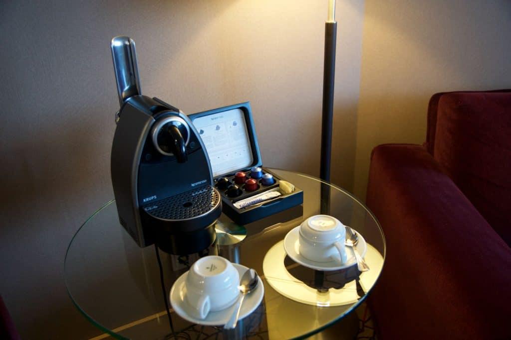 Mesa com cafeteira, xícaras e porta-cápsulas.
