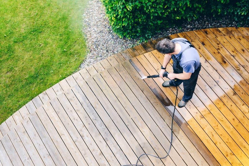 Na foto um homem lavando um deck de madeira.