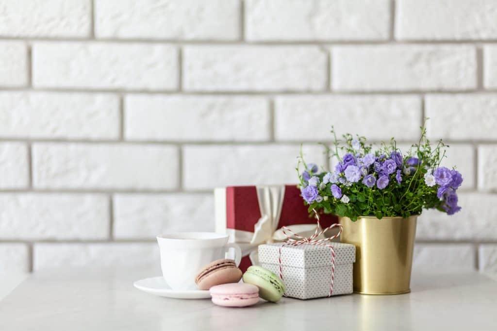 Na foto uma xícara, três macarrons dois presentes e um cachepot com flores roxas dentro.