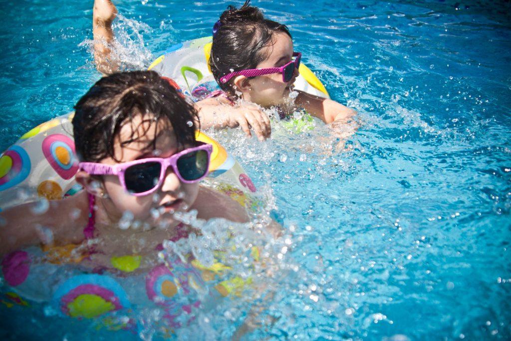 Duas meninas em suas boias dentro da piscina.