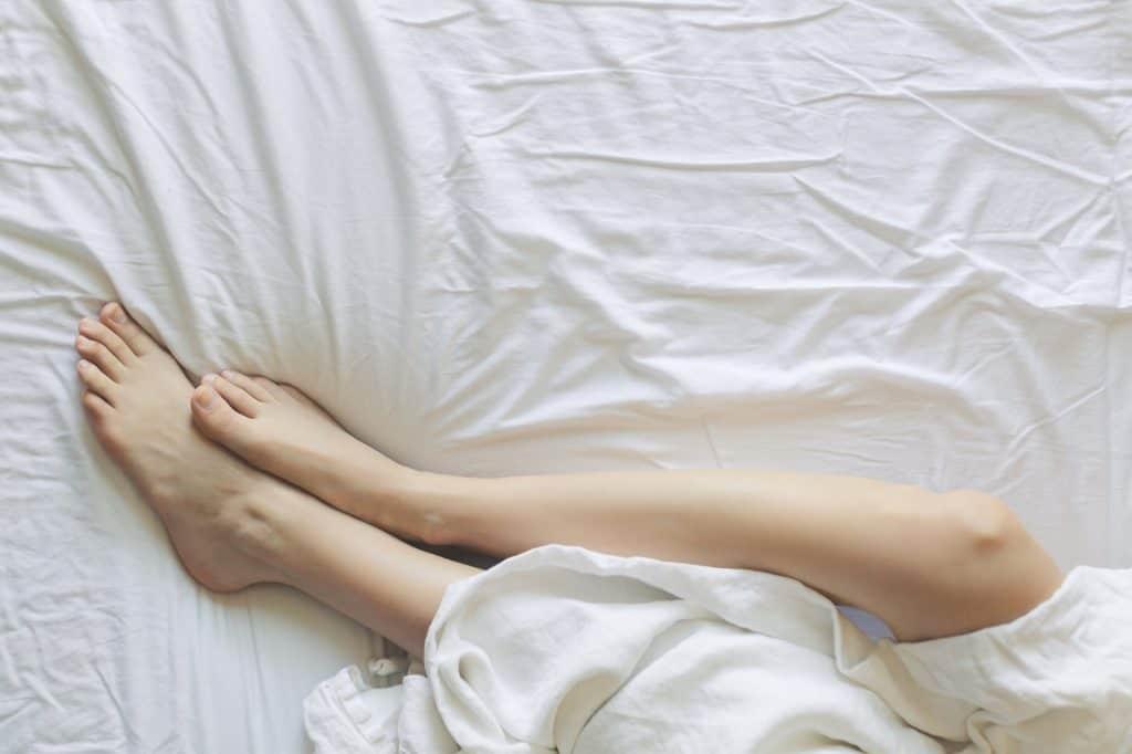 Foto tirada de cima que mostra as pernas de uma pessoa entrelaçada em um lençol, deitada em uma cama.