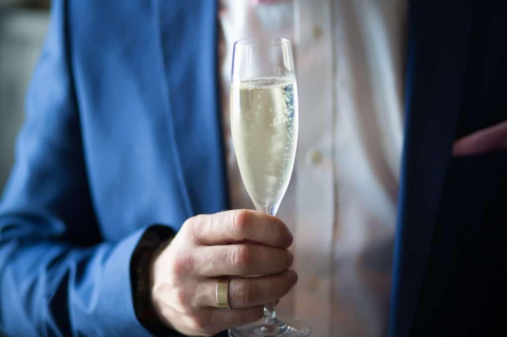 Foto que mostra um homem segurando uma taça de champagne na altura do peito, em uma mão com aliança dourada. Ele veste camisa social branca e blazer azul.