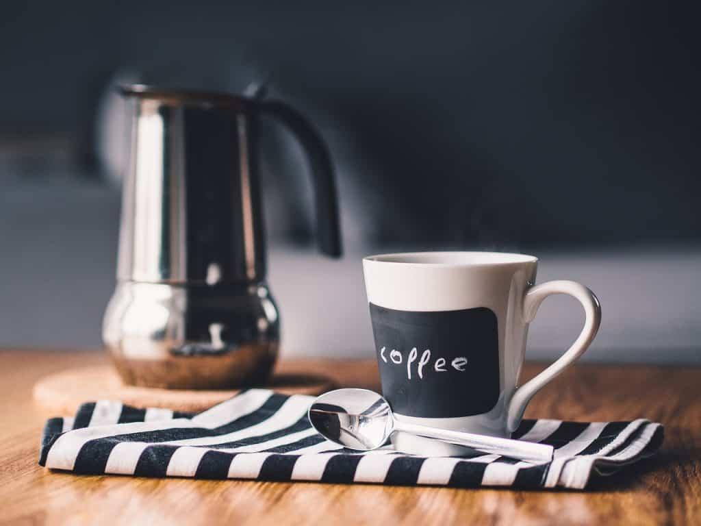 Leiteira e copo de café com colher em cima da mesa.