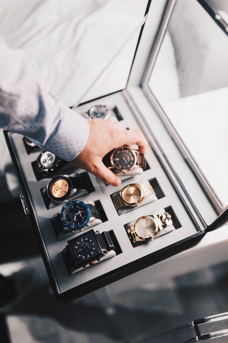 Imagem mostra uma mão segurando um relógio, entre uma coleção de outros nove relógios.