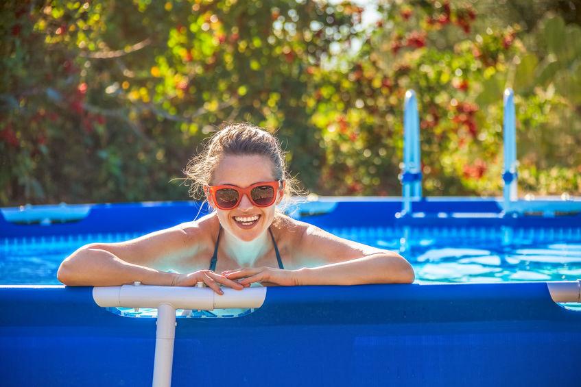 Mulher na beira de uma piscina de armação sorrindo.