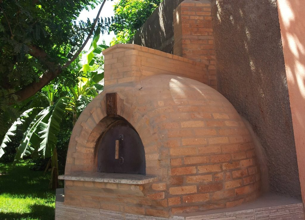 Forno a lenha em formato iglu, revestido externamente com tijolos, em área externa.