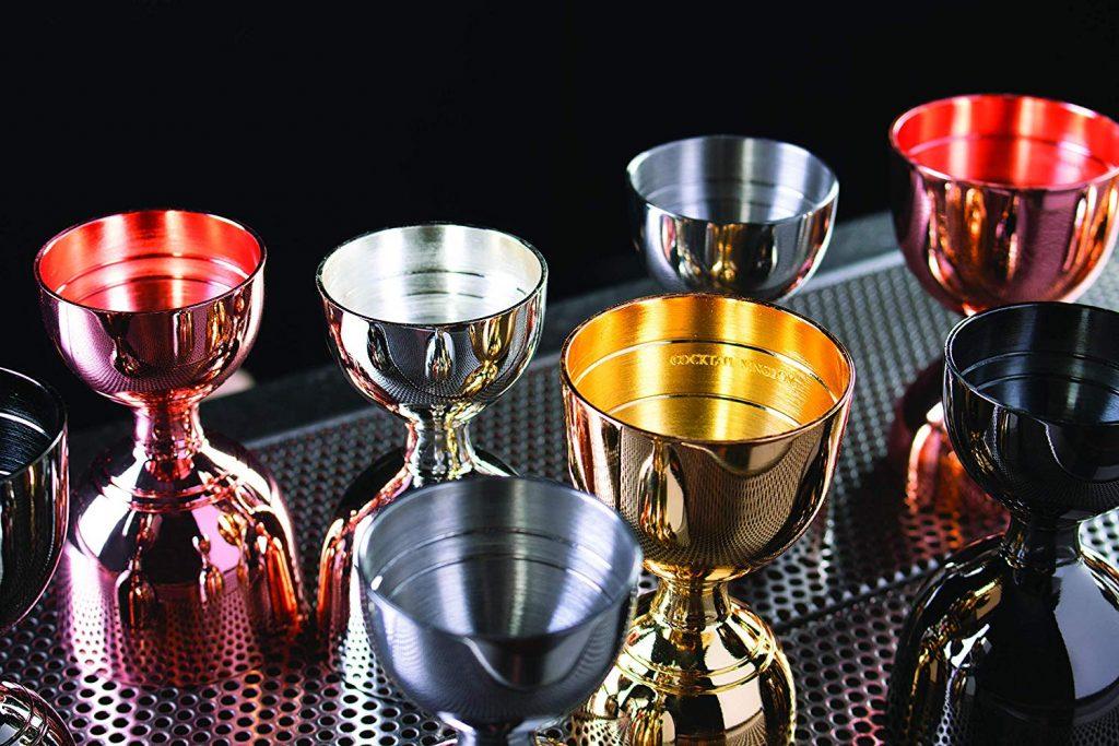 Vários dosadores estilo britânico, de diversas cores (prata, preto, amarelo, vermelho) estão em cima de uma superfície metalizada vazada com furinhos.