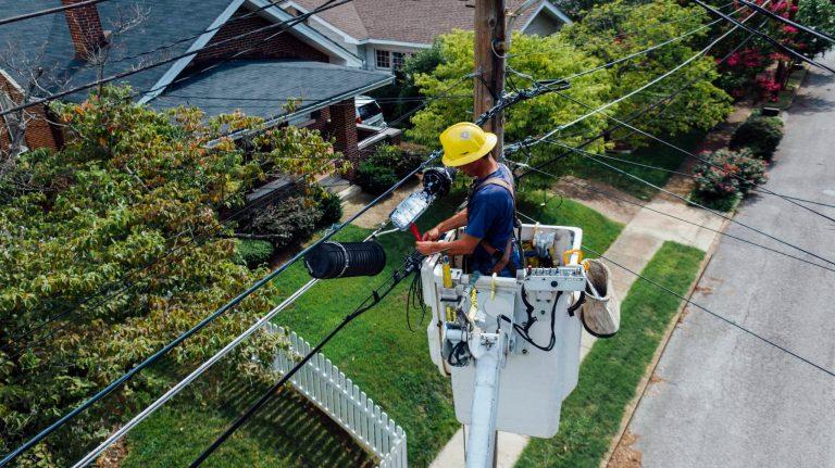 Imagem mostra um homem fazendo reparos na rede elétrica.